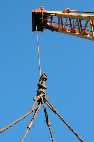 Industrial crane boom hoisting up a suspended load by cables